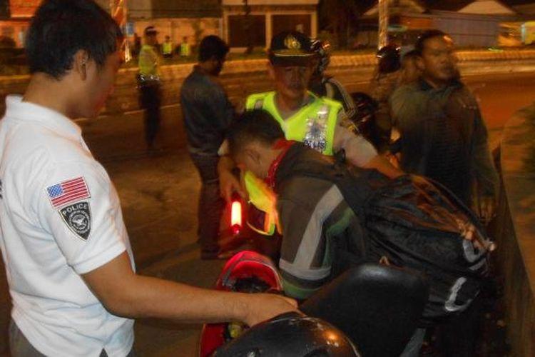 Petugas memeriksa pengendara motor saat operasi begal di alun-alun Demak, Sabtu (15/3/21015)