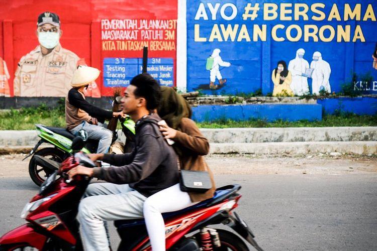 Pengendara melewati dinding yang dihiasi mural di Bukit Duri, Tebet, Jakarta pada Minggu (18/10/2020) sore.