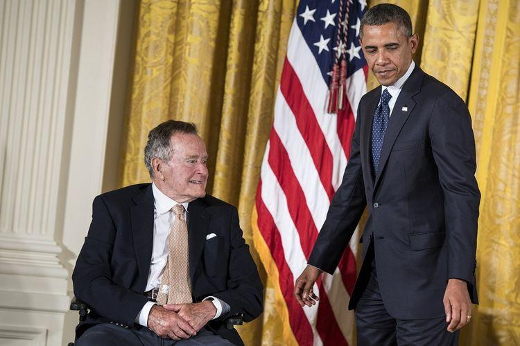 Mantan Presiden Amerika Serikat George HW Bush bersama Presiden aktif AS Barack Obama saat menghadiri acara di East Room, Gedung Putih, pada 15 Juli 2013. George Bush Senior meninggal Jumat (30/11/2018) dalam usia 94 tahun.