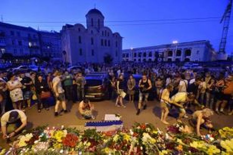 Warga meletakkan bunga dan lilin di depan Kedutaan Besar Belanda di Kiev, Kamis (17/7/2014), sebagai tanda dukacita atas jatuhnya pesawat malaysia Airlines MH17.