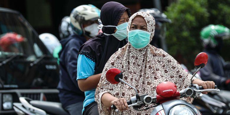 Warga menggunakan masker saat mengendarai sepeda motor di kawasan Mampang Prapatan, Jakarta Selatan, Senin (6/4/2020). Kebijakan wajib masker itu  tertuang dalam Seruan Gubernur Daerah Khusus Ibu Kota Jakarta Nomor 9 Tahun 2020 Tentang Penggunaan Masker Untuk Mencegah Penularan Corona Virus Disease (Covid-19).