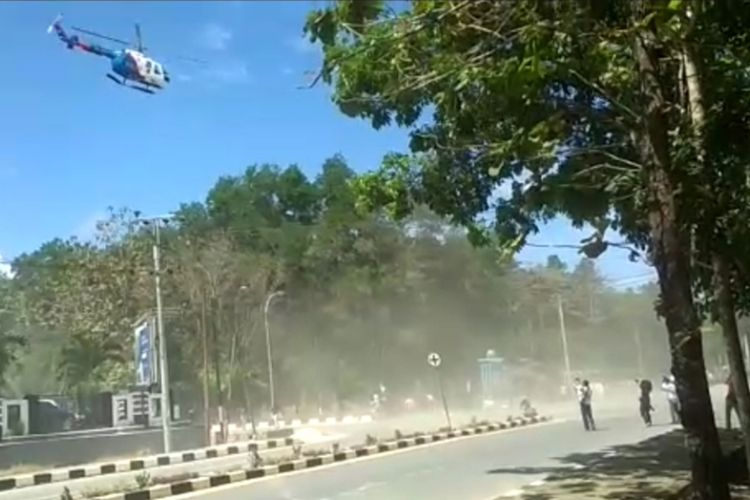 An Indonesian National Police helicopter disperses protesters in Kendari, Central Sulawesi on 26 September