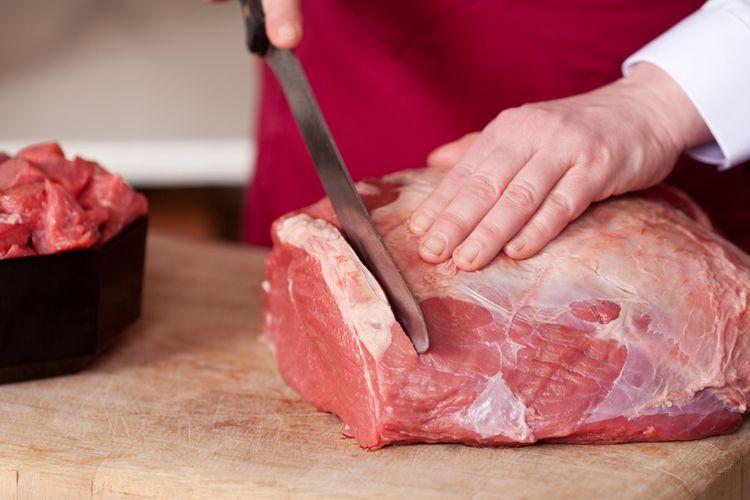 ilustrasi daging mentah yang sedang dipotong.