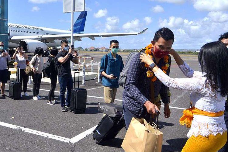 Petugas mengalungkan bunga untuk menyambut penumpang pesawat rute domestik yang tiba di Bandara Internasional I Gusti Ngurah Rai, Badung, Bali, Jumat (31/7/2020). Pemerintah Provinsi Bali mulai membuka sektor pariwisata bagi wisatawan domestik pada Jumat (31/7) dengan sejumlah persyaratan yang mengedepankan aspek kesehatan dan kualitas untuk memberi pelindungan, kenyamanan dan keamanan bagi wisatawan yang berkunjung selama masa pandemi Covid-19.