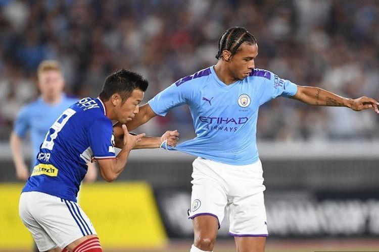 Gelandang Yokohama F Marinos, Takuya Kida, memperebutkan bola dengan pemain Manchester City, Leroy Sane, dalam pertandingan persahabatan antara Man City vs Yokohama F Marinos di Stadion Yokohama pada 27 Juli 2019.