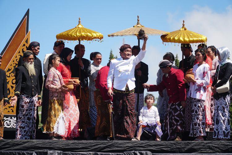 Kayang Ayuningtiyas Nugroho (duduk) saat menjalani ritual potong rambut gembel, Minggu (4/8/2019).