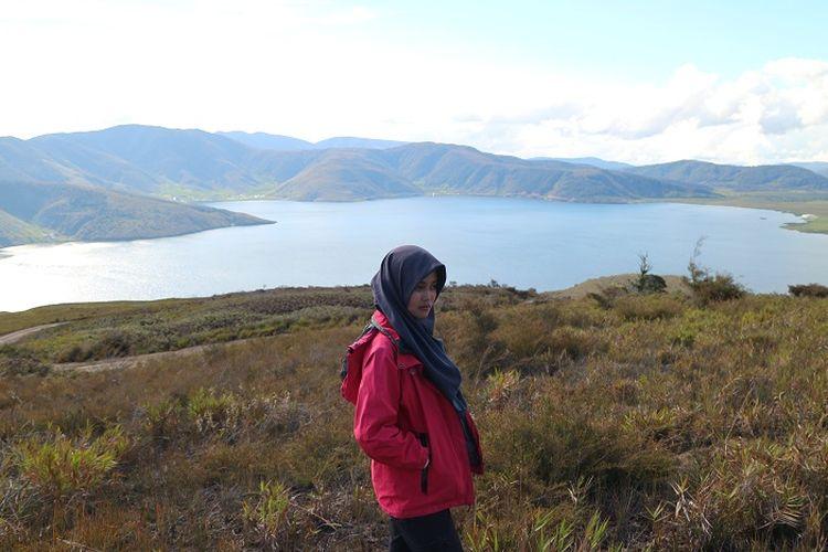 Seorang turis berfoto dengan latar pemandangan Danau Anggi Giji dari Bukit Kobrey, Distrik Sururey, Kabupaten Pegunungan Arfak, Papua Barat, Jumat (17/8/2018). Danau Anggi Giji merupakan obyek wisata yang ada di Pegunungan Arfak yang bisa dikunjungi oleh wisatawan.