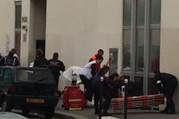 Polisi dan tim paramedis berkumpul di depan kantor majalah satir Charlie Hebdo di Paris, Perancis, (7/1/2015), setelah kantor majalah itu diserbu orang bersenjata yang menewaskan setidaknya 11 orang.