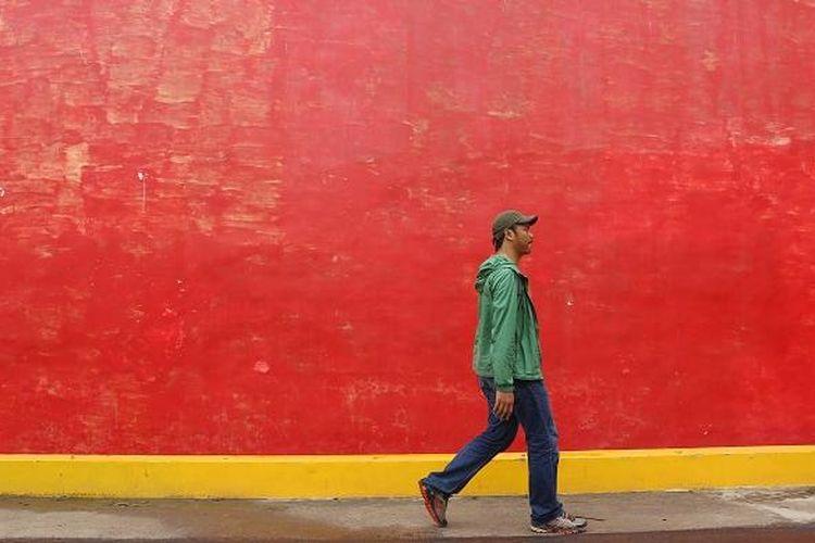 Wisatawan melewati tembok rumah merah atau juga dikenal dengan sebutan Tiongkok Kecil Heritage di Desa Karangturi, Kecamatan Lasem, Kabupaten Rembang, Jawa Tengah, Jumat (10/2/2017). Tiongkok Kecil Heritage adalah salah satu bangunan bergaya Cina Hindia di Desa Karangturi yang telah direnovasi.