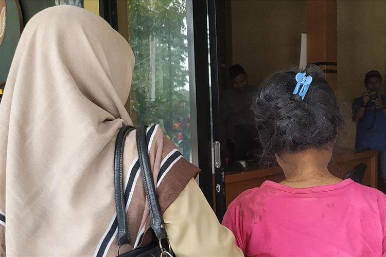 Am (kanan) didampingi kerabatnya di Polsek Cikidang, Sukabumi, Jawa Barat, Senin (15/7/2019).