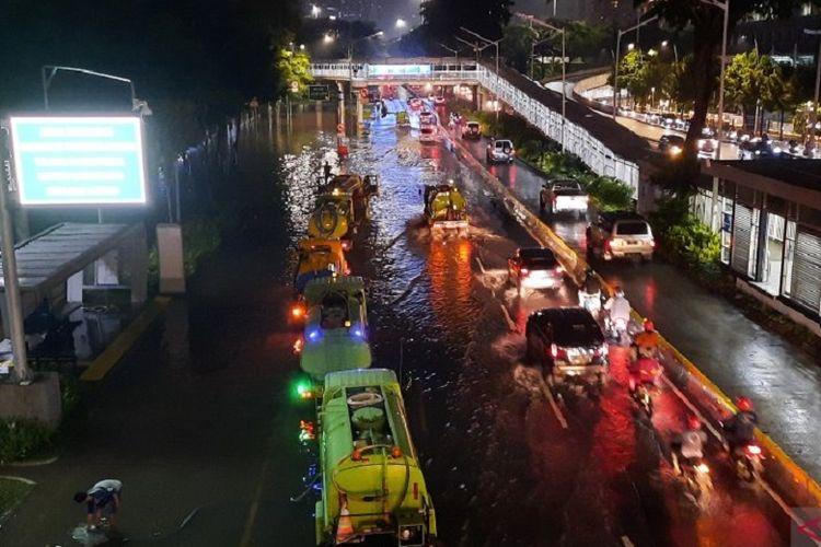 Antrean kendaraan melintas menuju jalur cepat Simpang Susun Semanggi arah Patung Senayan dan Blok M imbas banjir, Sabtu (20/2/2021) malam.