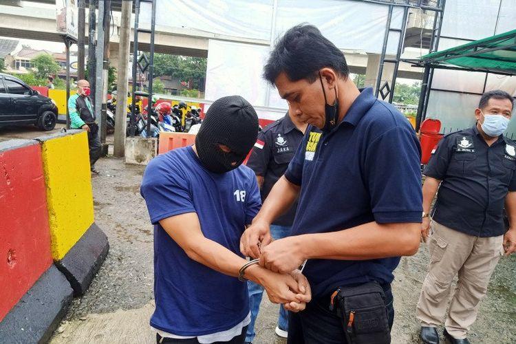 Polisi memborgol lengan tersangka kasus eksibisionis di Mapolsek Duren Sawit, Jakarta Timur, Kamis (21/1/2021). Aksi pelecehan seksual itu dilakukan tersangka kepada istri komedian Isa Bajaj berinisial RM.