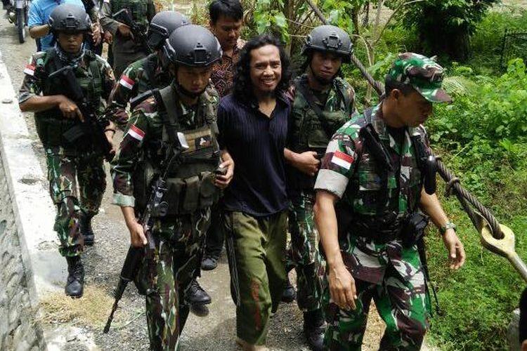 Basri alias Bagong dibawa dengan pengawalan ketat Satuan Tugas Tinombala 2016 di Poso, Sulawesi Tengah, Rabu (14/9/2016).