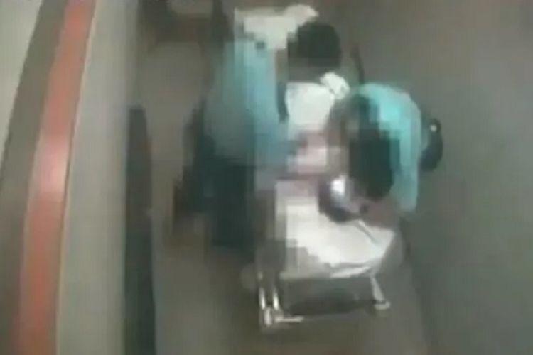 Tangkapan layar rekaman CCTV rumah sakit yang menunjukkan dua oknum polisi melakukan pemukulan terhadap seorang pria di atas brankar.