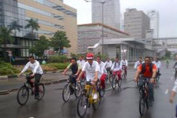 Presiden RI Joko Widodo bersepeda dalam kondisi hujan di Car free day, Minggu (1/1/2015).