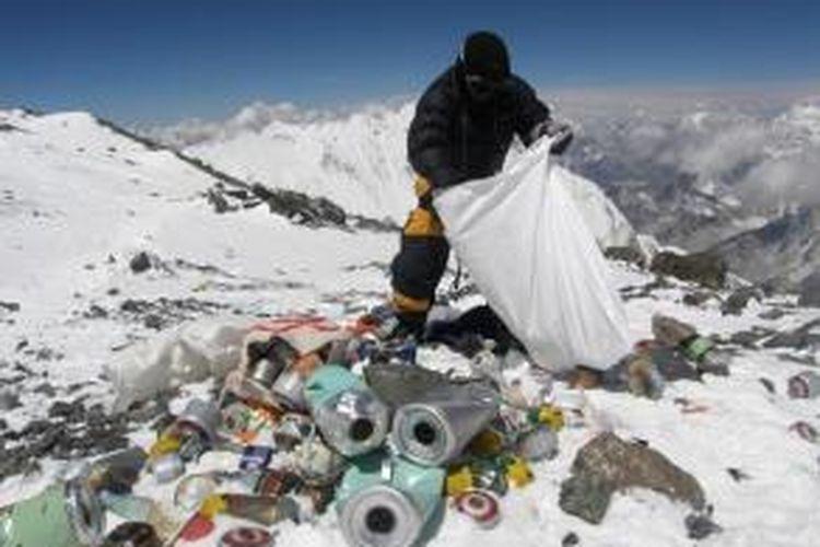 Dalam foto yang diambil pada 23 Mei 2010 ini, seorang sherpa asal Nepal sedang membersihkan sampah yang ditinggalkan para pendaki Gunung Everest di ketinggian 8.000 meter di atas permukaan laut. Mulai April mendatang, pemerintah Nepal mengharuskan tiap pendaki membawa turun setidaknya delapan kilogram sampah dari puncak gunung itu.