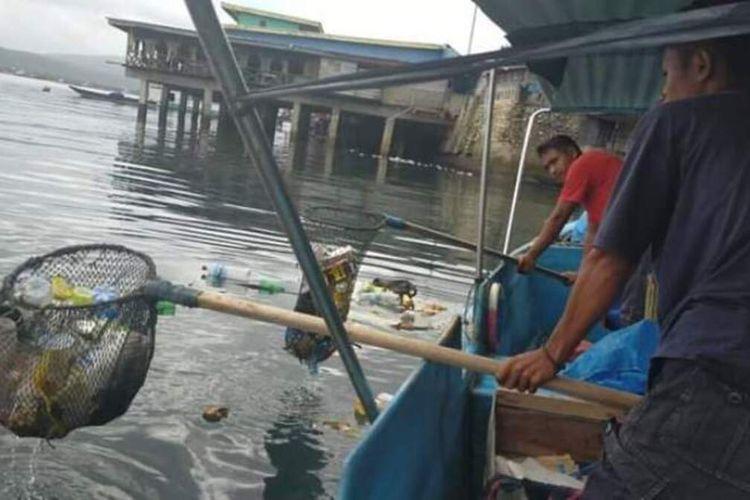 Dua petugas kebersihan dari Dinas Lingkungan Hidup dan Persampahan Kota Ambon sedang mengangkut sampah di laut Teluk Ambon atau tak jauh dari pasar ikan di Mardika, Ambon, Kamis (4/6/2020)