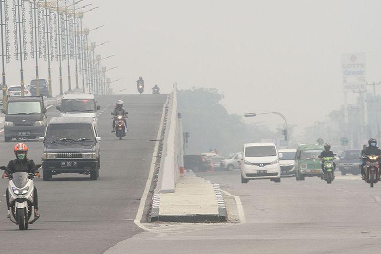 Pengendara kendaraan bermotor menggunakan masker pelindung pernafasan ketika melintas di Jalan Soekarno Hatta, Pekanbaru, Riau, Sabtu (7/9/2019). Hal itu dilakukan untuk meminimalisir dampak asap akibat karhutla.