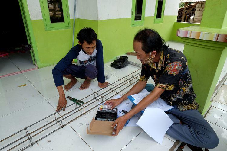 Petugas survei migrasi televisi digital memberikan penjelasan mengenai penggunaan perangkat set to box (STB) kepada warga RT 2 Nambo Udik, Cikande, Serang, Banten, Kamis, (10/6/2021). Kemenkominfo terus mempermudah migrasi ke siaran TV digital dengan mendorong ketersediaan STB.