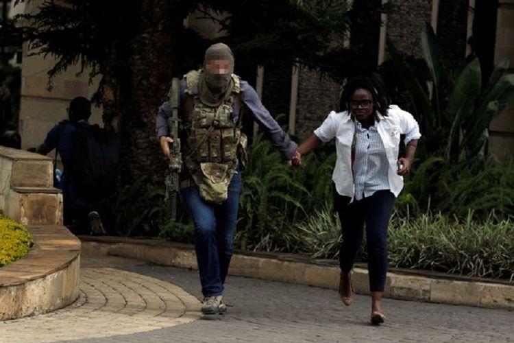 Seorang anggota pasukan elite Inggris SAS berlari bersama warga sipil ketika terjadi penyerangan di kawasan hotel mewah di Nairobi, Kenya, pada Selasa (15/1/2019).
