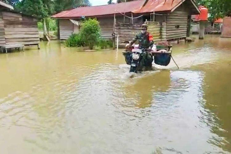 Babinsa Koramil 10/Kunto Darussalam Kopda Jantri Istani terobos banjir hampir semeter saat menyalurkan bantuan sembako kepada para korban banjir di Desa Kasang Mungkal, Kecamatan Bonai Darussalam, Kabupaten Rohul, Riau, Rabu (31/3/2021).