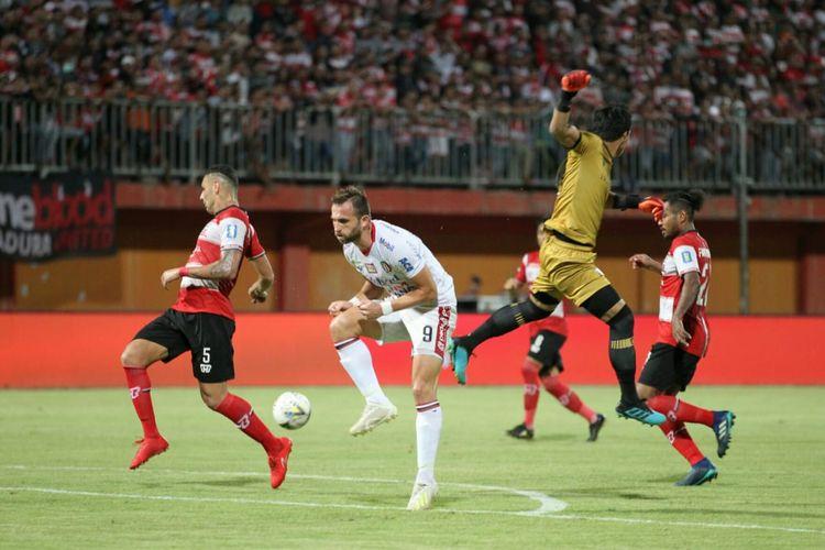 Penyerang Bali United, Ilija Spasojevic, berjibaku dengan para pemain Madura United pada lanjutan pekan ke-15 Liga 1 2019 di Stadion Gelora Ratu Pamelingan, Selasa (20/8/2019).