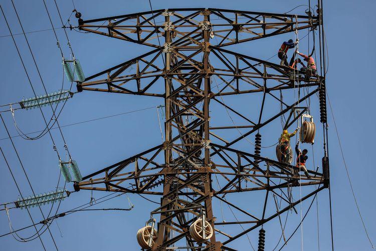 Sejumlah pekerja menyelesaikan pekerjaan rekonduktoring atau penggantian kabel konduktor jalur transmisi SUTT (Saluran Udara Tegangan Tinggi) 150.00 volt (150 kV) dari gardu induk Angke ke Karet lama di kawasan Petamburan, Tanah Abang, Jakarta, Sabtu (27/7/2019). Penambahan jaringan listrik di tujukan untuk memperluas jangkauan distribusi pasokan listrik di Jakarta raya dan sekitarnya serta sekaligus meningkatkan pelayanan terhadap konsumen PT PLN.