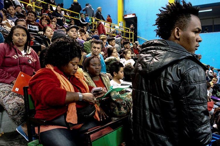 Para migran mengantre untuk mengurus izin tinggal mereka kepada otoritas migrasi di Stadion Victor Jara, Santiago, Chile.