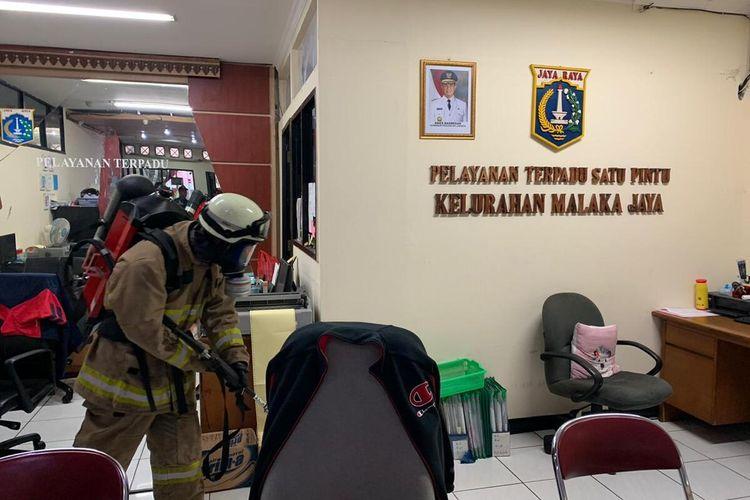 Petugas Damkar Jakarta Timur saat menyemprotkan cairan disinfektan di Kantor Kelurahan Malaka Jaya, Jakarta Timur, Jumat (20/3/2020).