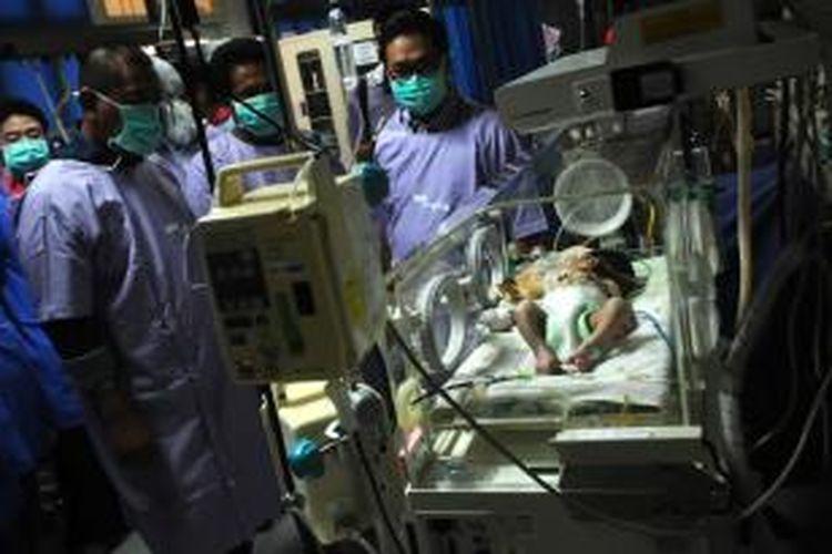Wakil Gubernur Jawa Barat Deddy Mizwar menjenguk bayi kembar parasit bernama Ginan Septian Nugraha di ruang Neonatal Intensive Care Unit (NICU) RSHS Bandung, Minggu (29/9/2013).
