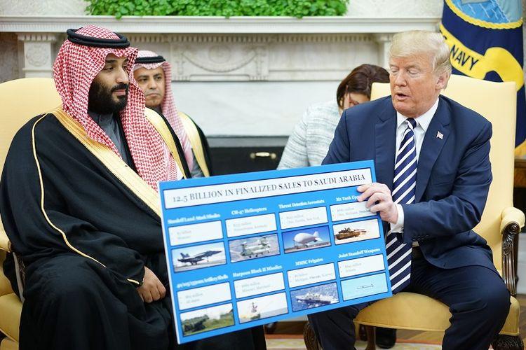 Presiden AS Donald Trump memegang papan yang menunjukkan rencana penjualan berbagai senjata ke Arab Saudi saat bertemu Pangeran Mohammed bin Salam di Ruang Oval, Gedung Putih, Rabu (20/3/2018).