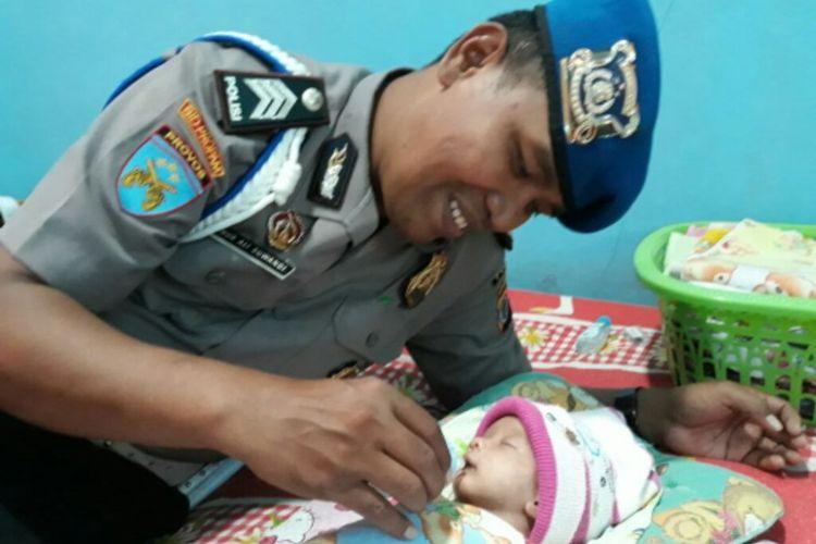 Brigadir Nur Ali Suwandi saat memberikan susu kepada bayi yang diasuhnya, Muhammad Tito Karnavian.