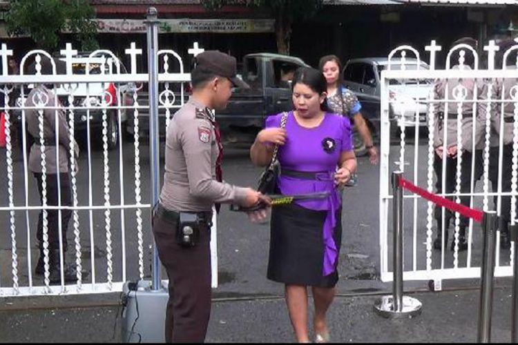 Pengunjung Gereja Santo Yosef Pangkal Pinang melewati pemeriksaan metal detektor