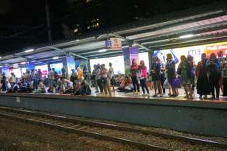 Penumpang menumpuk di peron 2 Stasiun Sudirman akibat lamanya KRL tujuan Bogor yang tiba. Sebagian dari mereka terpaksa duduk di pinggir peron, Rabu (6/4/2016).