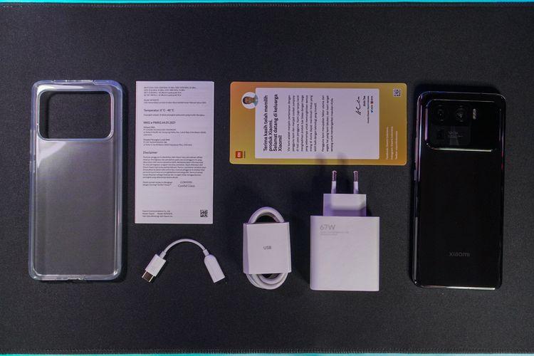 Aksesori-aksesori pelengkap di kemasan penjualan Xiaomi Mi 11 Ultra, mencakup casing silikon transparan, fast charger 67 watt (USB A), kabel USB A ke USB C, kabel adapter audio 3,5mm ke USB C, serta booklet panduan dan surat terima kasih. Ada juga sebuah SIM card ejector tool