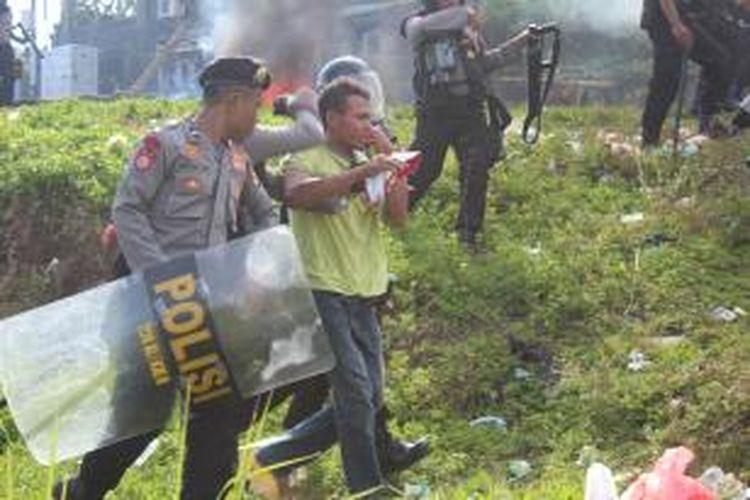 Polisi mengamankan seorang mahasiswa Universitas Darusalam (Unidar) Ambon, yang berunjuk rasa di kampus mereka di kawasan Wara, Air Kuning Kecamatan Sirimau berakhir bentrokan, Selasa (29/10/2013)