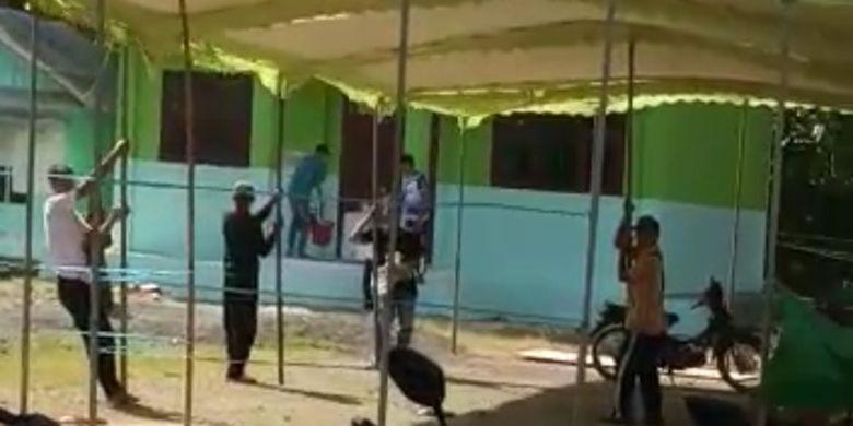 Panitia pemungutan suara salah satu TPS di Desa Batumalang, Kecamatan Cimerak, Kabupaten Pangandaran, memegangi tiang TPS saat wilayah tersebut diterjang angin kencang, Selasa siang (8/12/2020).