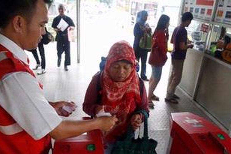 Petugas berjaga menerima tiket kertas di depan mesin  tiket elektronik yang belum beroperasi di Terminal Kalideres, Jakarta, Minggu ( 7/4/2013). Mulai Mei 2013, semua koridor transjakarta berencana akan menggunakan tiket elektronik (e-ticketing) dan sstem tiket manual akan dihilangkan.