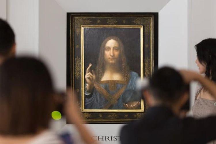 Orang-orang memotret lukisan Salvator Mundi yang tengah dipamerkan. Lukisan ini diragukan karena bola kristal yang dibawa Yesus Kristus tidak membelokkan cahaya.