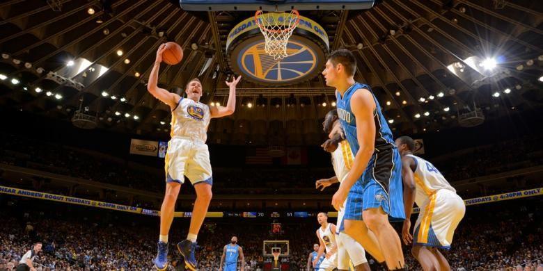 Pebasket Golden State Warriors David Lee (kiri) melakukan rebound saat melawan Orlando Magic di Oracle Arena, Selasa (18/3/2014). Warriors menang 103-89.