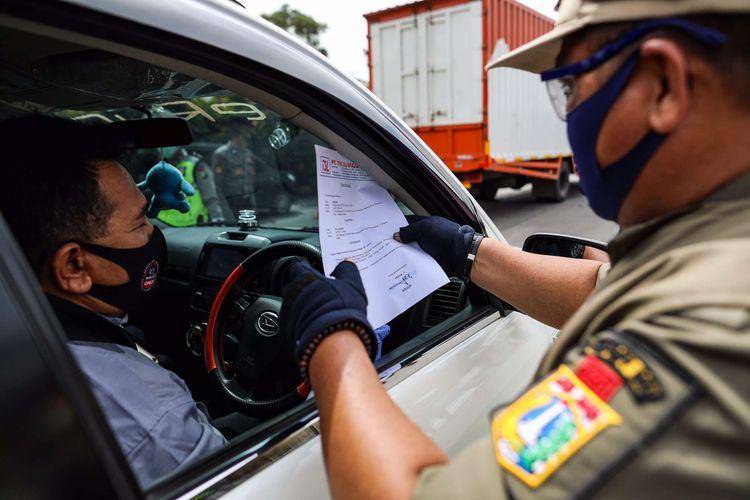 Petugas gabungan memeriksa kendaraan di gerbang tol Cikupa, Kabupaten Tangerang, Banten, Kamis (28/5/2020). Selama operasi pemeriksaan kepada masyarakat dari luar Jabodetabek yang ingin masuk ke Jakarta diharuskan menunjukkan SIKM, berdasarkan peraturan gubernur (Pergub) Nomor 47 Tahun 2020 yang mewajibkan membawa SIKM sebagai syarat memasuki wilayah Jakarta.