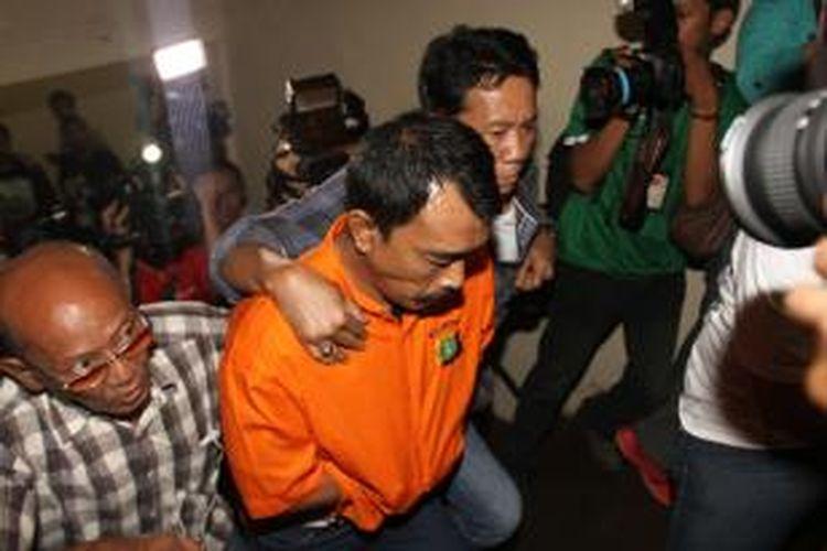 Surya Hakim digiring polisi untuk diperlihatkan saat rilis di Polda Metro Jaya, Jakarta Pusat, Rabu (16/10/2013). Polisi telah menangkap dua orang tersangka pembunuh Holly Angela Ayu, Surya Hakim dan Abdul Latif, sedangkan satu pelaku tewas sedangkan dua lagi masih buron. Polisi juga memeriksa suami Holly yang juga auditor BPK,Gatot Supiartono.