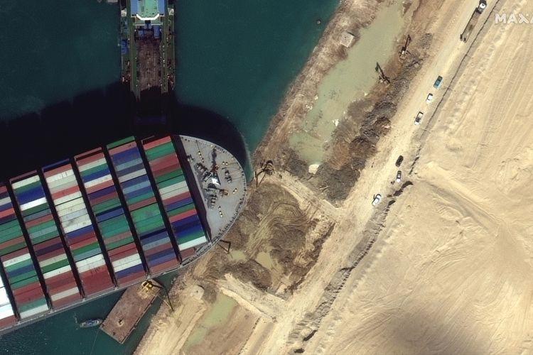 Foto satelit dari Maxar Technologies memperlihatkan kapal Ever Given masih tersangkut di sisi Terusan Suez, Mesir, pada Sabtu (27/3/2021). Petugas bersiap melakukan cara-cara baru agar kapal kargo raksasa ini terbebas, dan kondisi Terusan Suez macet segera berakhir.