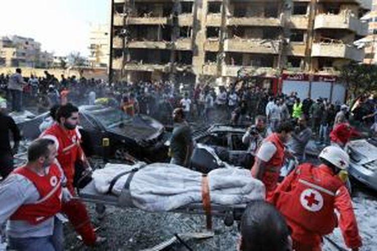 Petugas Palang Merah Lebanon bekerja keras mengevakuasi korban ledakan di luar kedutaan besar Iran di Beirut, Selasa (19/11/2013). Sejauh ini 22 orang tewas, termasuk satu staf kedutaan besar akibat ledakan itu.