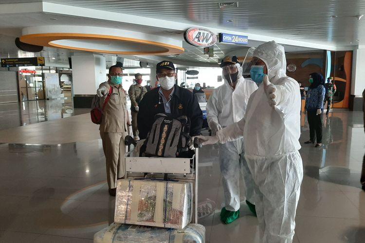 Salah satu penumpang PMI sedang diarahkan petugas untuk menunggu proses evakuasi dijemput oleh Tim Gugus Tugas Covid-19.
