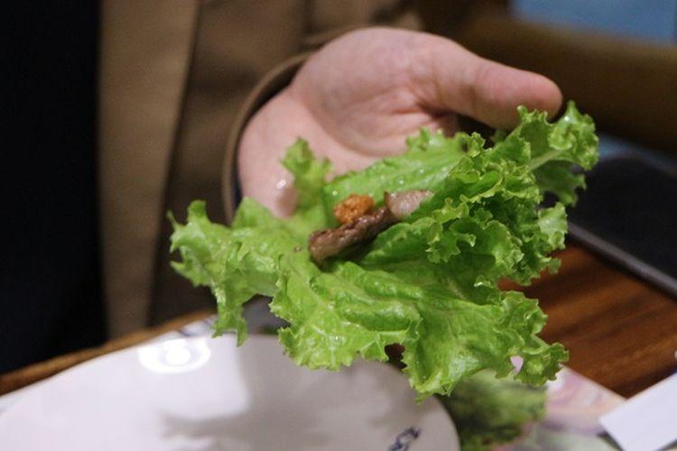Langkah kedua dalam Ssam adalah menambahkan daging, sayuran, dan saus di atas daun yang telah dipilih.