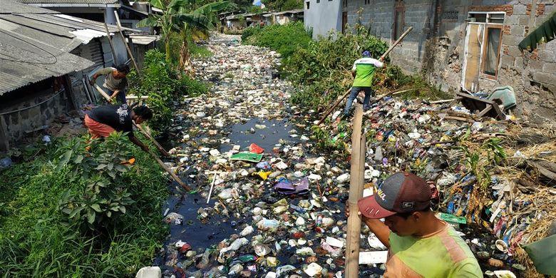 Warga bersama unsur koramil, kelurahan, dan Polsek Babelan membersihkan tutupan sampah di Kali Bahagia, Kabupaten Bekasi menggunakan peralatan sederhana, Selasa (30/7/2019).