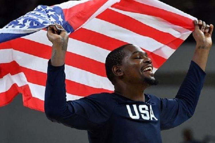 Kevin Durant mengibarkan bendera Amerika Serikat seusai timnya memenangi medali emas Olimpiade 2016 usai final versus Serbia, Minggu (21/8/2016).