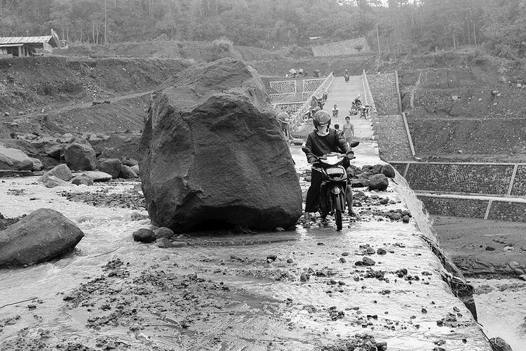 Warga nekat melitas di DAM Kali Apu di Desa Wonolelo, Kecamatan Sawangan, Magelang, yang baru beberapa minggu selesai dibangun, kembali rusak diterjang lahar dingin. Hingga Sabtu (5/11), material lahar dingin masih berada di tengah jembatan, mengakibatkan aktivitas warga terganggu. Jembatan itu menjadi akses terdekat bagi warga Desa Tlogolele, Kecamatan Selo, Kabupaten Boyolali untuk menuju pusat Kecamatan Selo.   Kompas/Amanda Putri (UTI) 05-11-2011