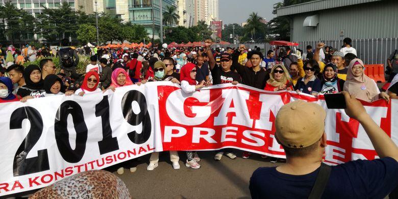 Sejumlah warga tampak berjalan kaki dengan spanduk sembari memakai kaus dan kaus #2019GantiPresiden di Bundaran HI, Jakarta, Minggu (29/4/2018).